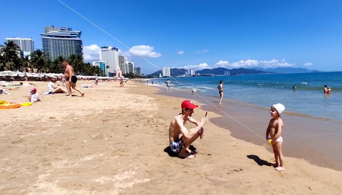 Hai cha con người du khách đến từ châu Âu vẫn vô tư chơi thả diều trên biển Nha Trang
